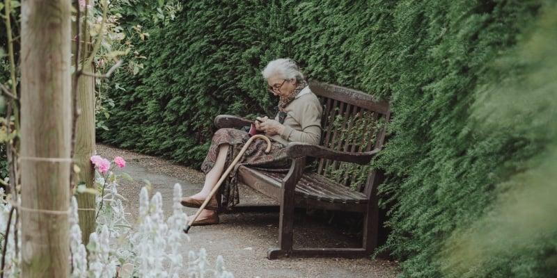 elderly woman sitting on a garden bench