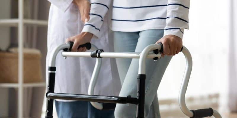 Medical professional assisting a person with walker