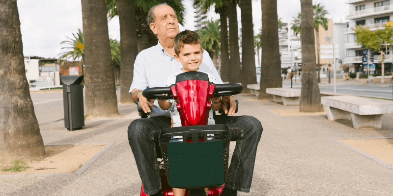 Man and child riding an electric wheelchair