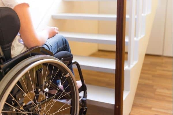 Disabled person on wheelchair near staircase