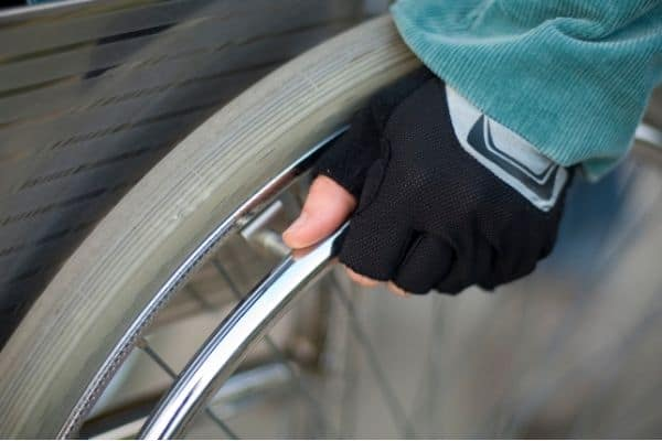 Person on a wheelchair with mesh gloves