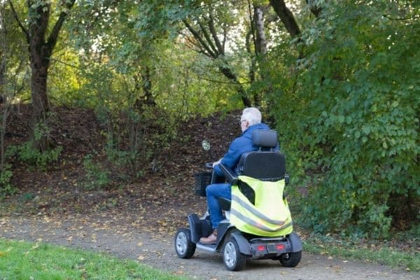 Man on mobility scooter traveling on forest trail