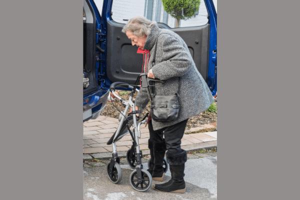 Elderly folding rollator near a car