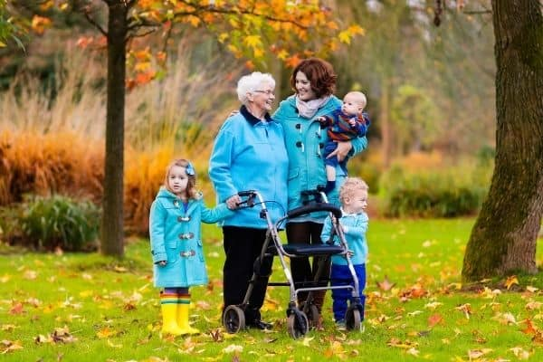 Elderly on rollator with family