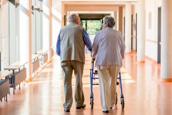 Two elderlies walking with one using a rollator