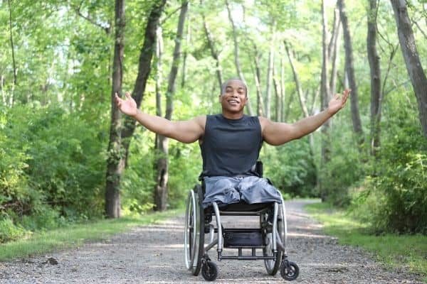 Healthy amputee on a wheelchair with trees on the background