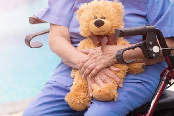 Person sitting on a rollator while holding a stuffed toy