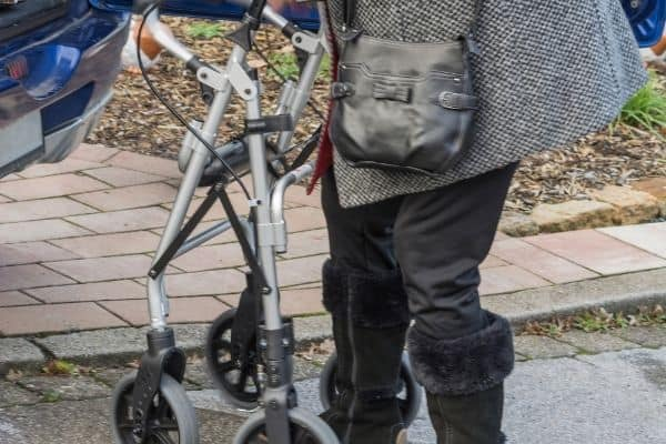 Person folding a rollator for travel