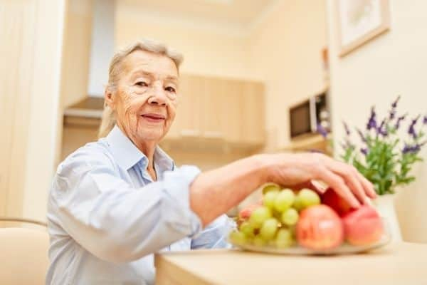 Elderly woman at home with a bowl of fruits