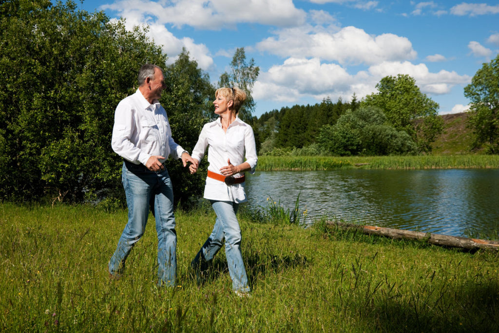 Early retiree couple walking in long grass near water on a sunny day
