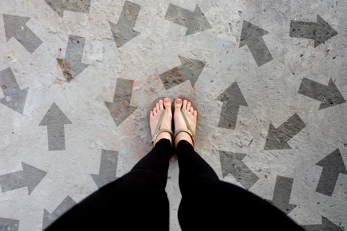 Feet in sandals surrounded by arrows - representing career change choices