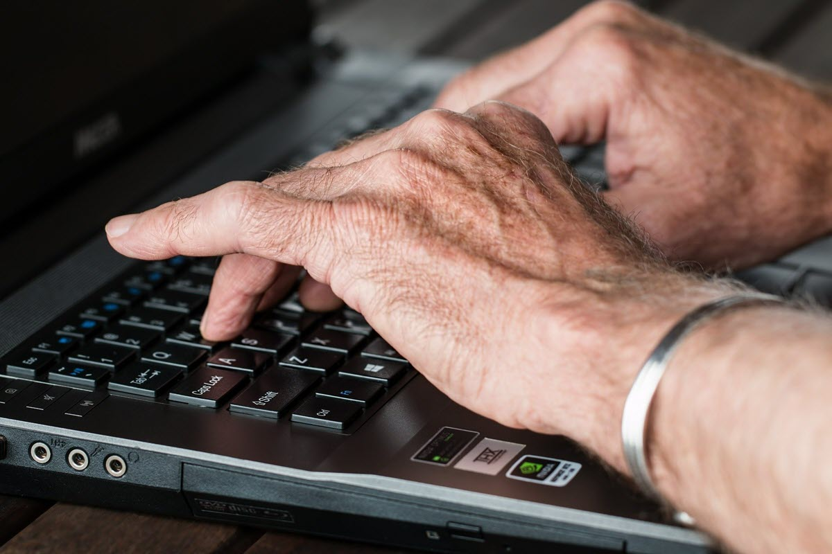 Older man hands typing email on a laptop