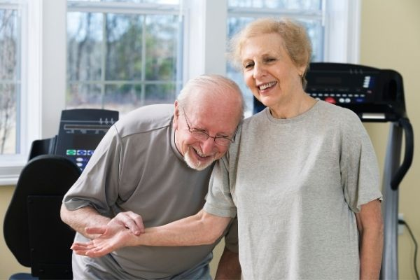 Senior couple with exercise equipment at home