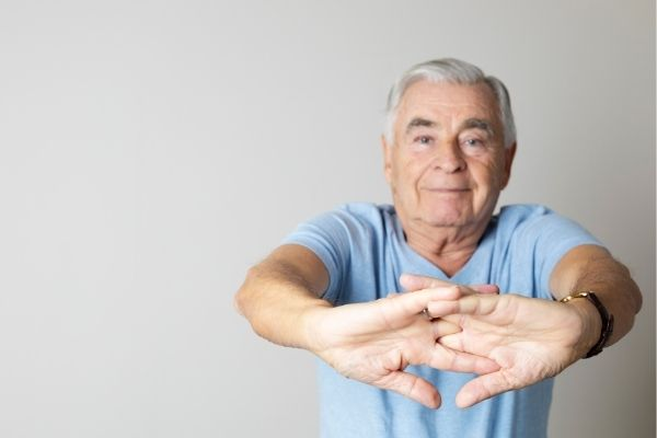 Elderly man stretching out arms and fingers