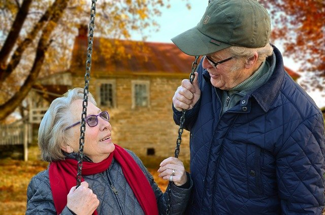 Elderly couple - woman in swing and husband talking to her