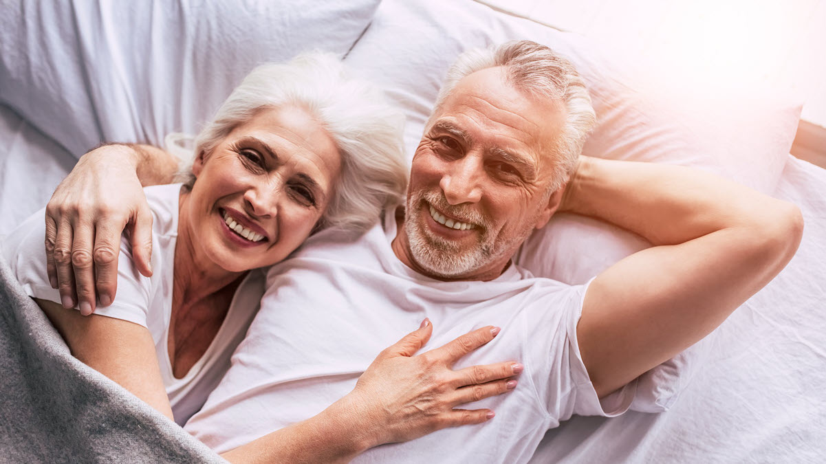 Older couple with gray hair smiling in bed together